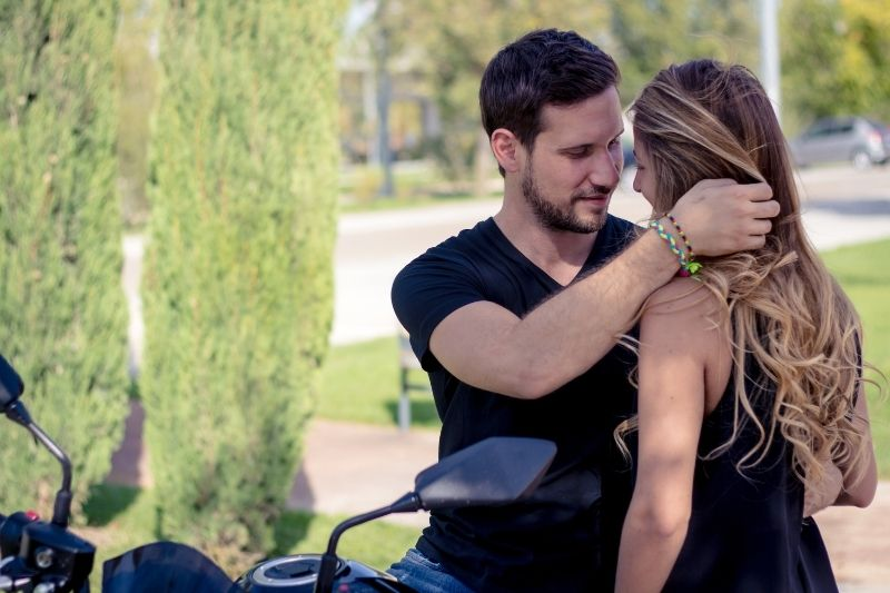 man holding woman's hair while sitting on a big bike in the park