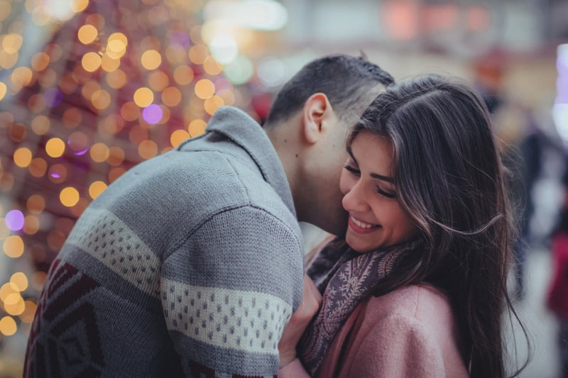 man kissing on woman at her neck outdoors near a big christmas tree