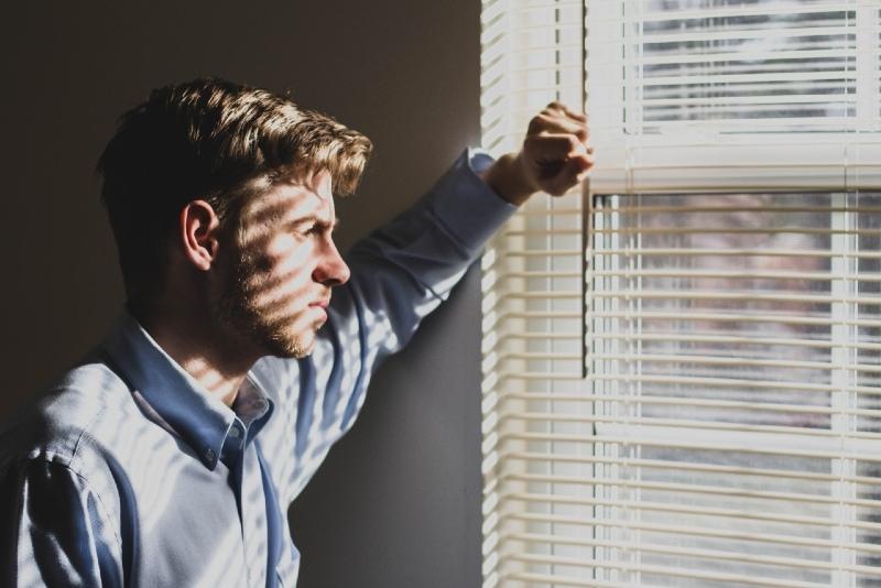 man in blue shirt looking through window