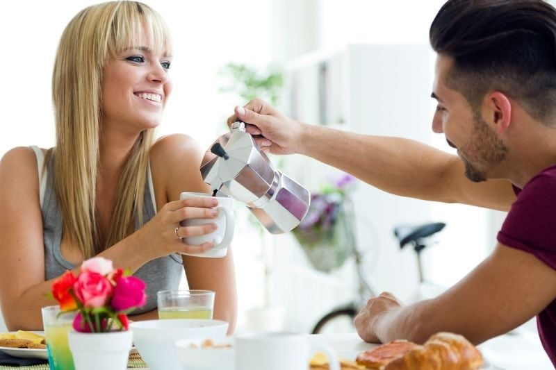 man pouring coffee in the woman's cup during breakfast in the kitchen