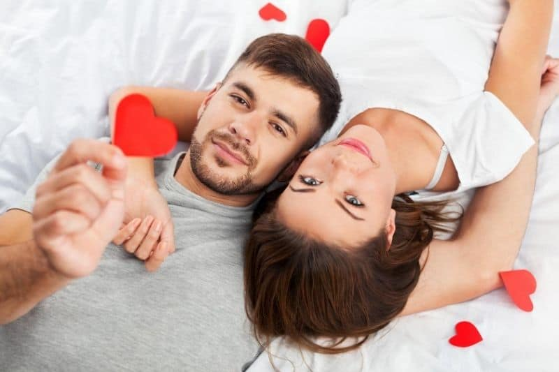 man showing paper heart with a woman beside her lying in opposite direction
