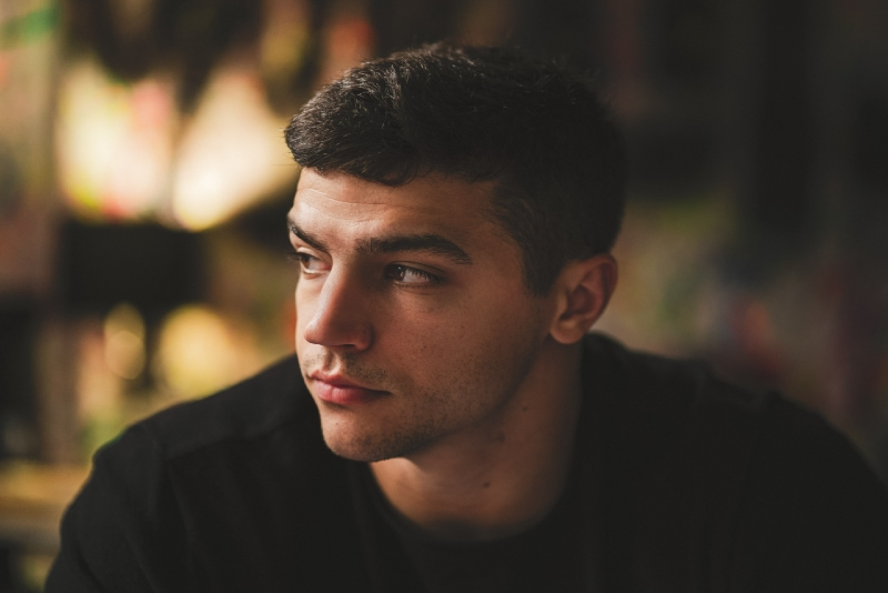 man in black sweatshirt sitting indoor