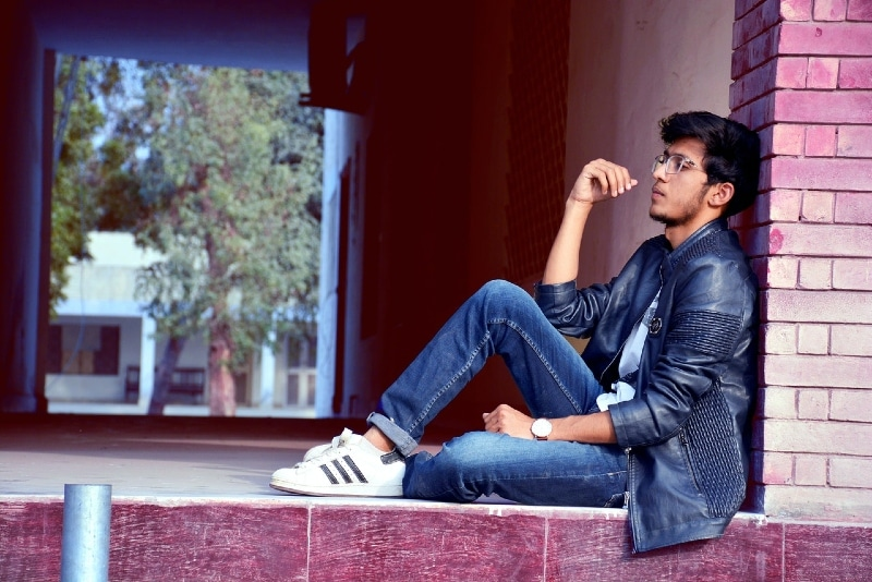 man in denim jacket sitting on floor