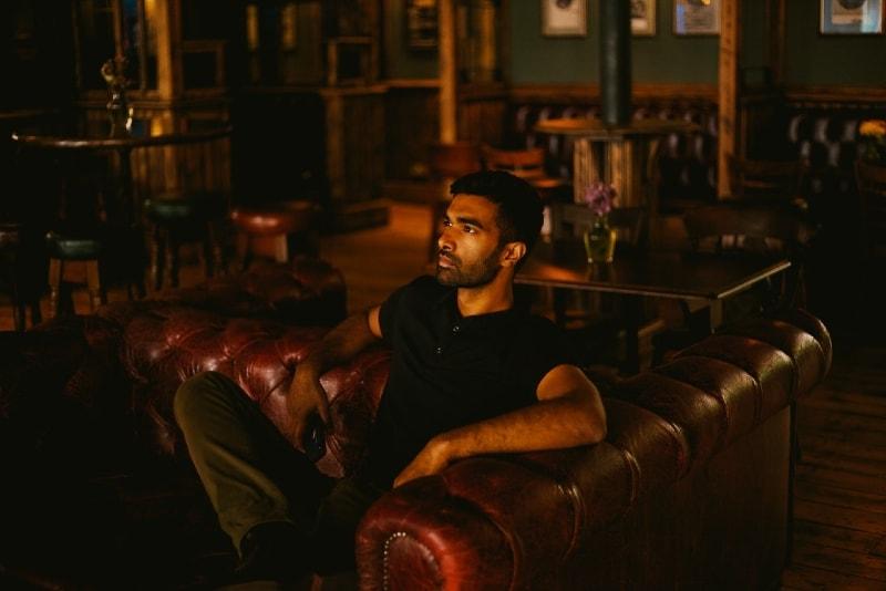 man in black shirt sitting on sofa