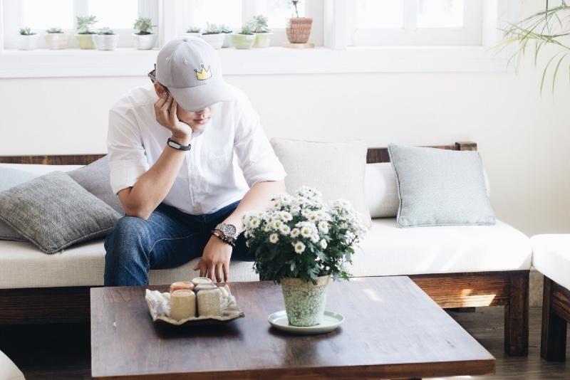 man in white shirt sitting on sofa near coffee table