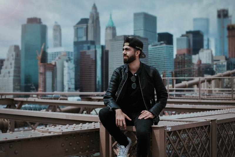 man in black jacket sitting on steel construction