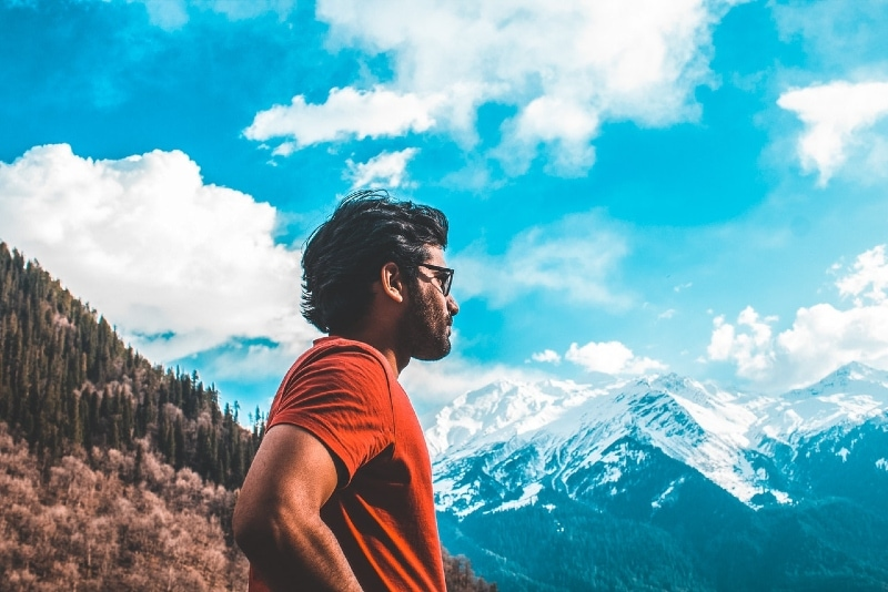 man in orange t-shirt standing near mountain