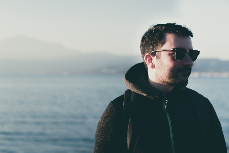 man with sunglasses standing near water