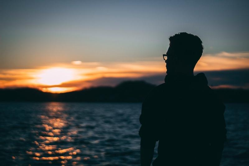 man standing near water during sunrise