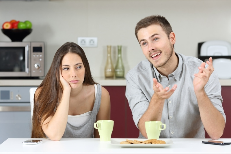 happy man talking to woman while sitting at table