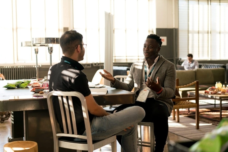 man talking to another man while sitting on chair