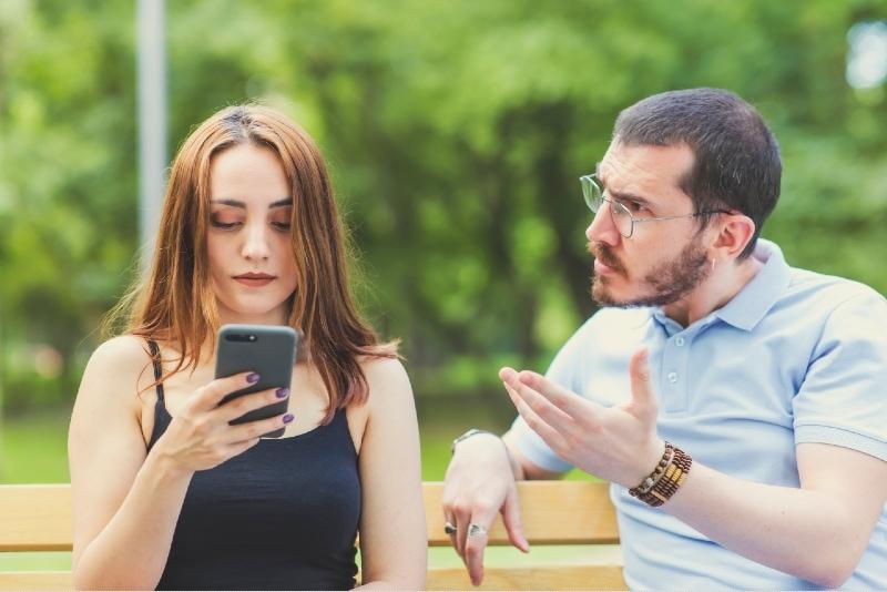 man talking to woman while sitting on bench