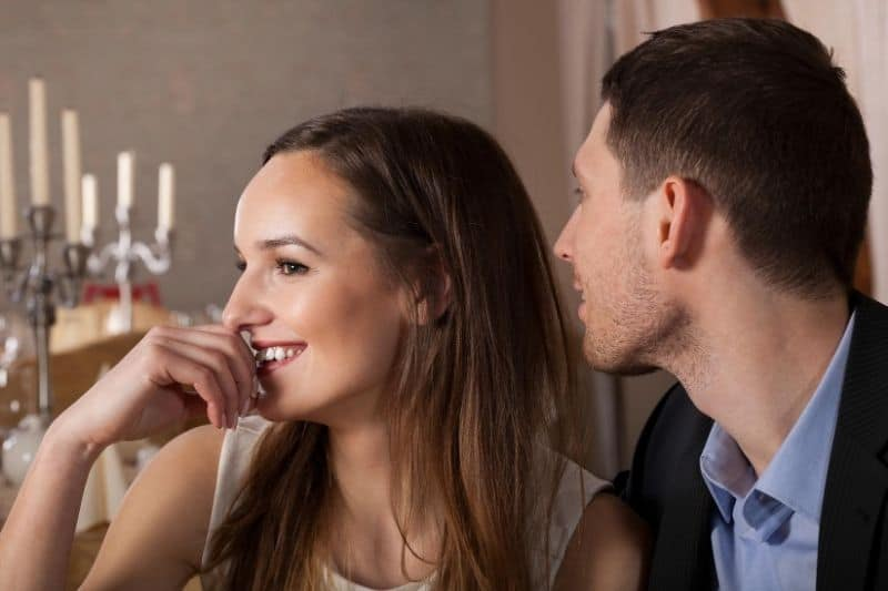 man whispering to the woman while having dinner date and the woman giggles