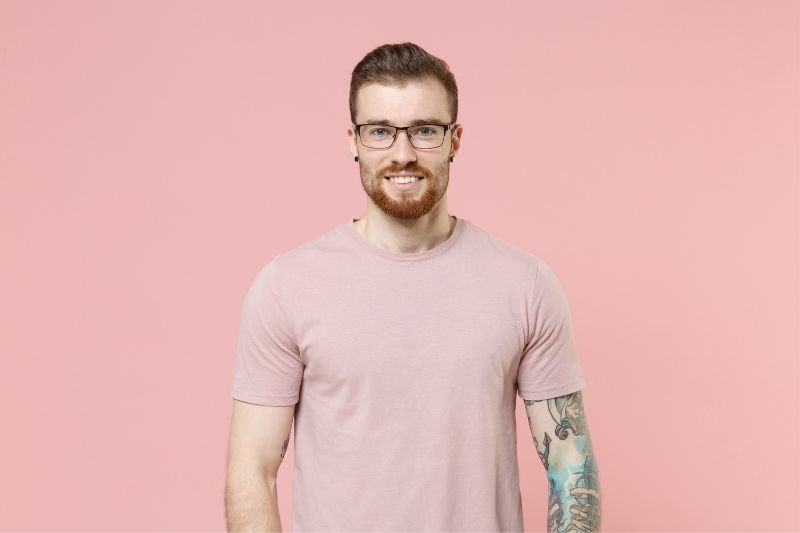 man with tattoo and ear piercing wearing eyeglasses and pink shirt standing against a pink wall