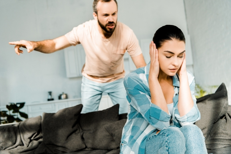 man yelling at woman while standing near sofa
