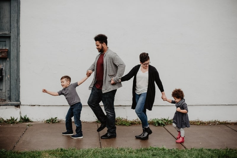 parents and kids walking at the street