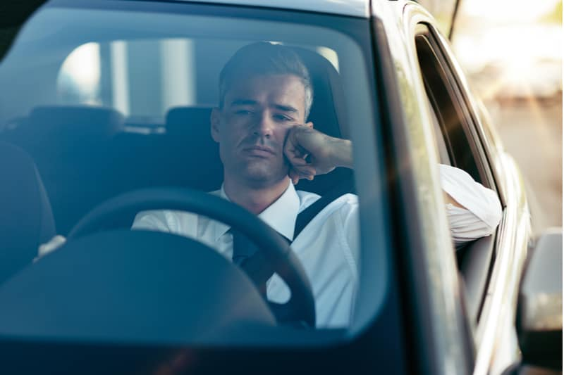 pensive businessman riding his car outdoors