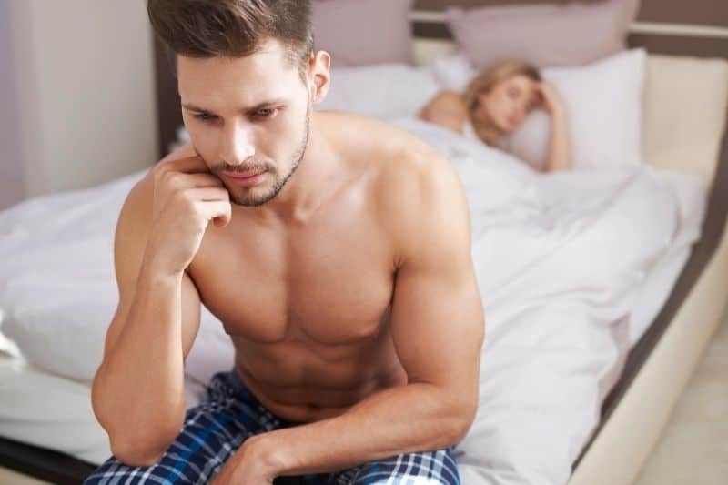 pensive man at bed half naked with a woman sleeping in bed