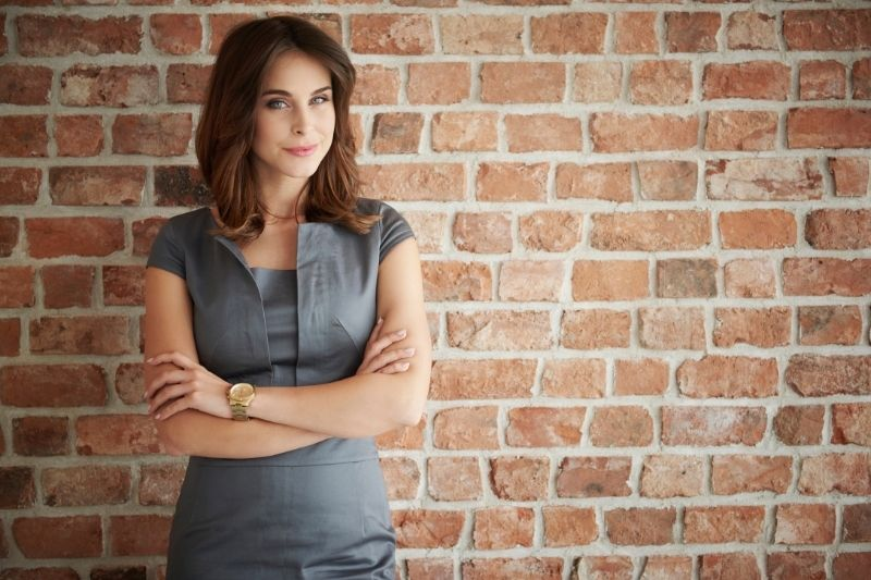 pensive woman standing against brown brick wall with arms crossed