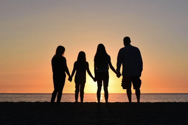 four people holding hands while looking at sea