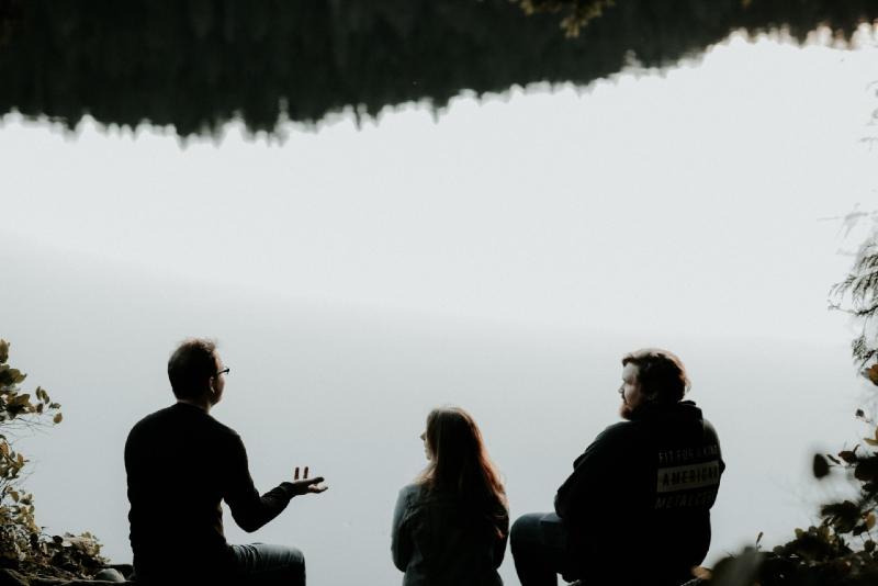 three people sitting near water and talking