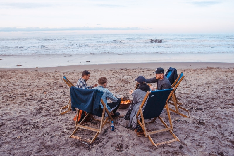 group of people sitting on beach near fire pit