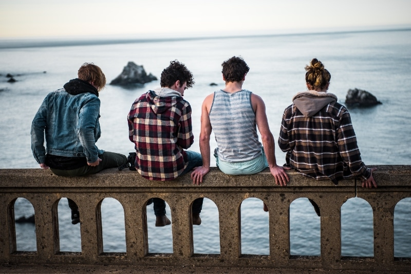 four people sitting on bench looking at sea