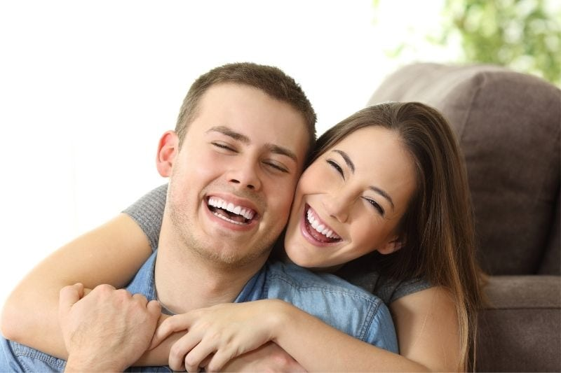 perfect white smile shown by the happy couple hugging inside the livingroom