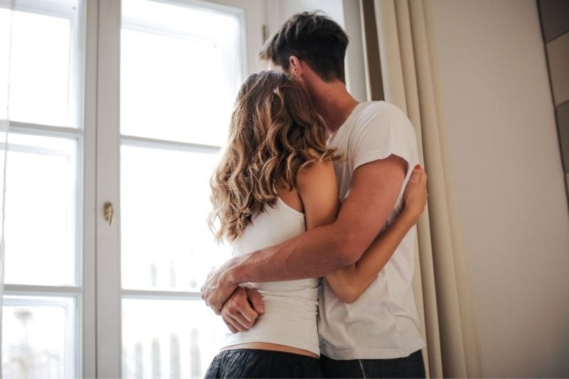 photo of a couple embracing each other near the windows of house