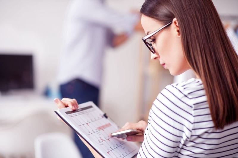 pleasant woman holding a calendar making a schedule while sitting