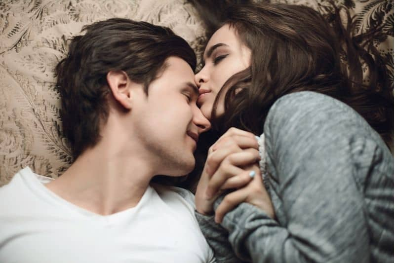 pretty brunette girl and guy lying down in bed closing eyes and hugging