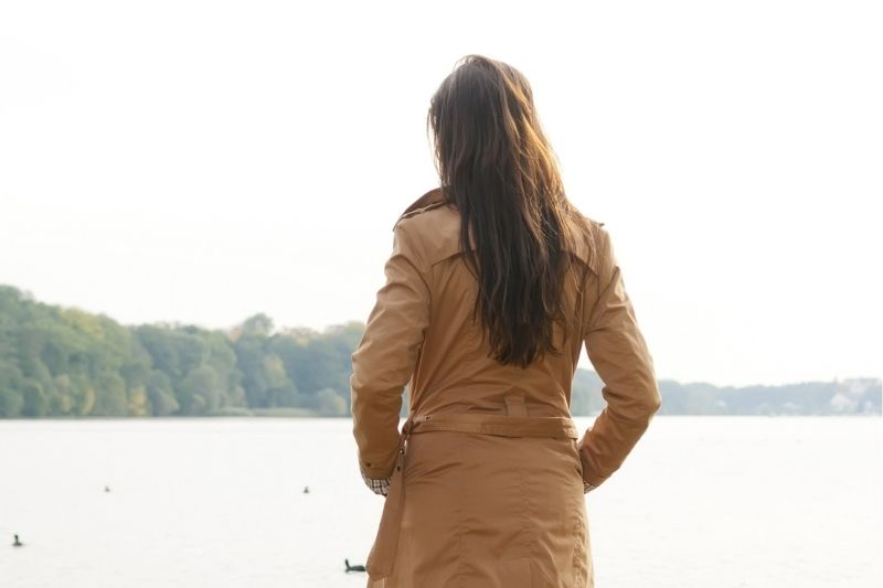 rear view of a woman standing in front of a body of water wearing brown trench coat