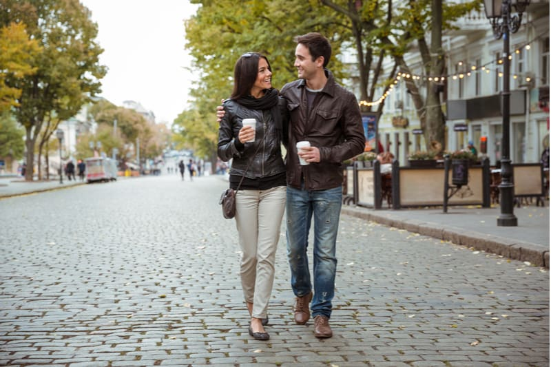 romantic happy couple walking along the street grabbing a cup of coffee