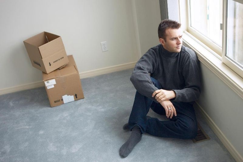sad man in an empty room sitting thinking and looking out the window