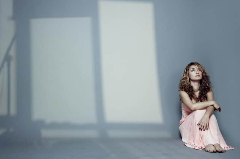sad woman sitting on the floor indoors with shadows of the windows
