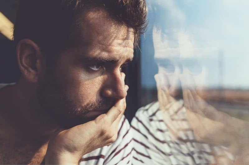 sad young man looking thru the window in focus