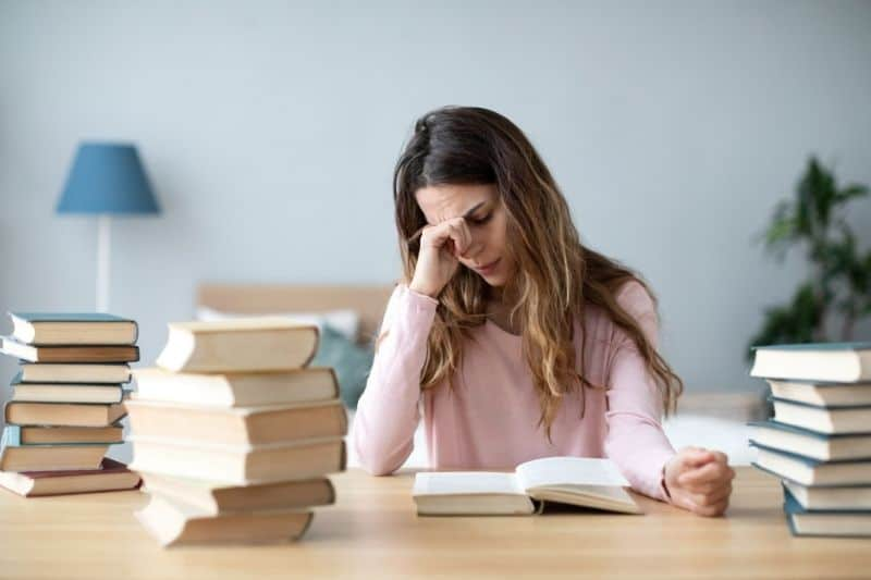 sad young woman with books on home desk reading sad