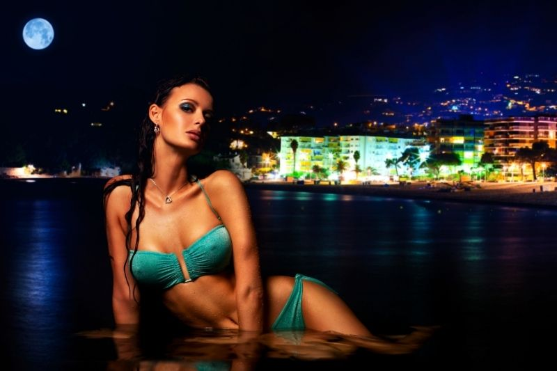 sexy woman on water wearing green two piece swimwear under the moon and far from the city
