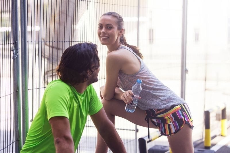 sexy young woman exercising with a man looking at her