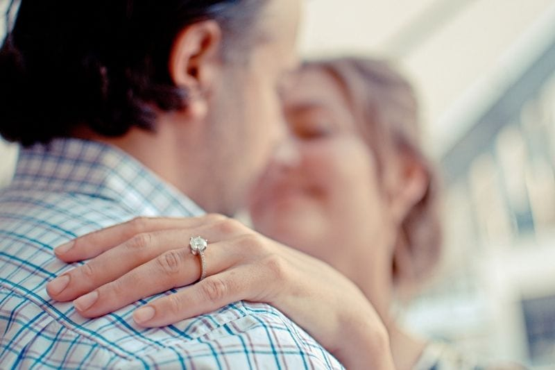 shallow focus photo of couple hugging with focus on the ring on woman's ring finger