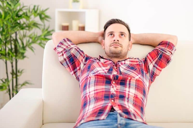 shot of a pensive man looking depressed lying in the sofa at home