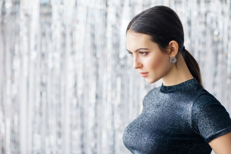 sideview of a sexy beautiful woman wearing black glittery top standing near silver curtains