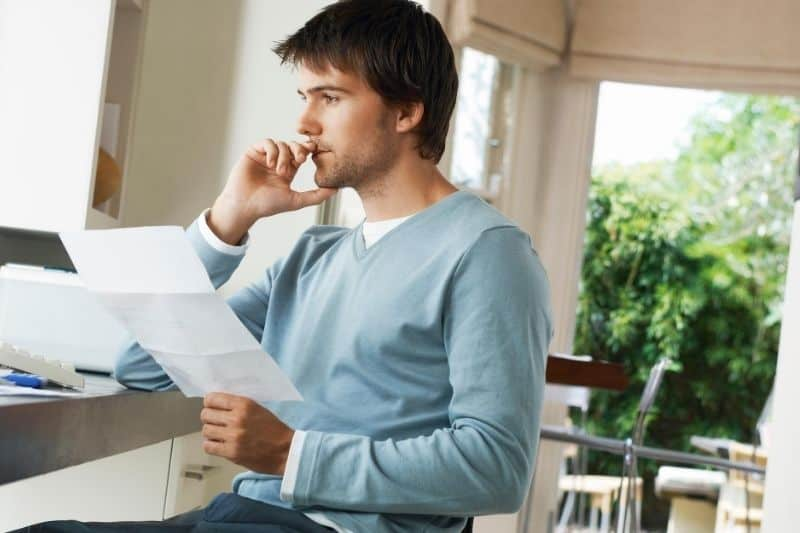 sideview of a worried man looking at bills at home
