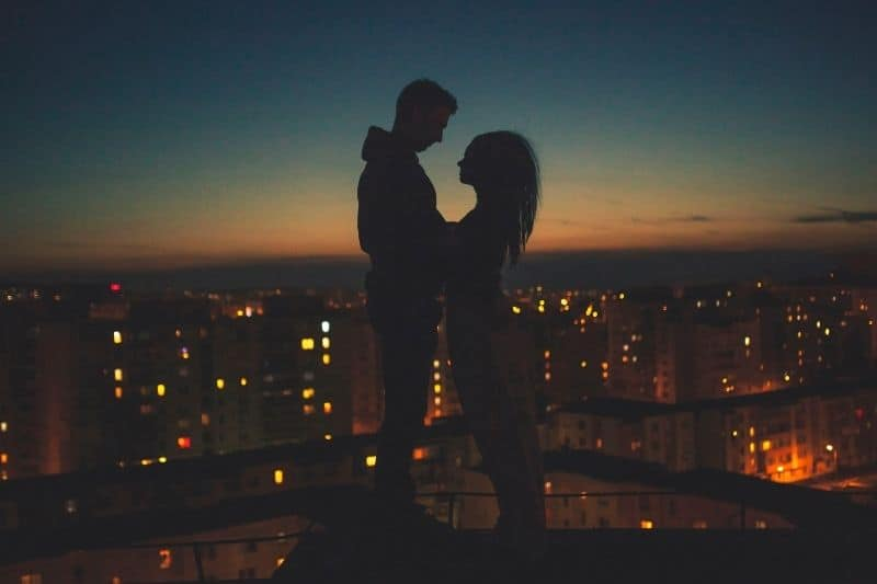 silhouette of a couple with the city as the background