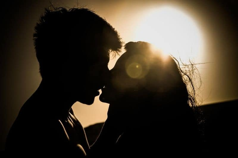 silhouette of couple kissing against the sunset
