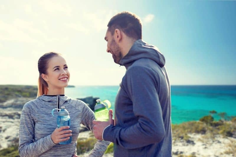 smiling couple drinking water from the drinker wearing athletic wear near the sea