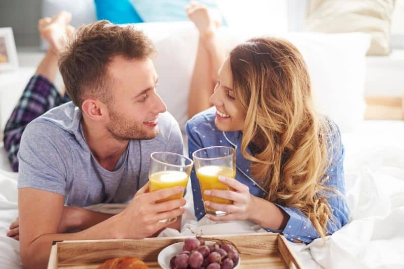 smiling couple eating healthy breakfast at bed