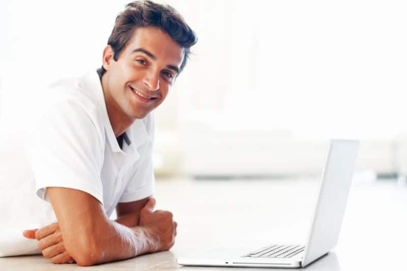smiling man with laptop looking at the camera during the daytime