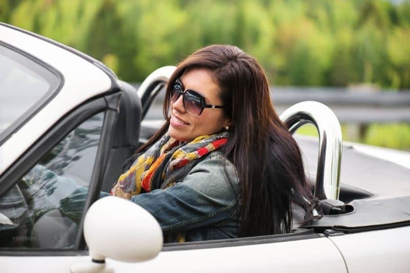smiling woman driving in a top down car wearing a jacket and sunglasses