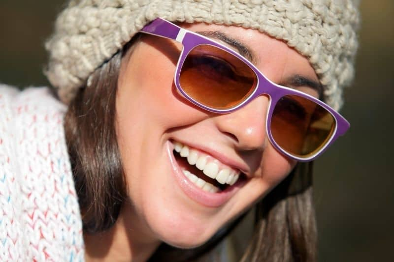 smiling woman with sunglasses and a bonnet in focus